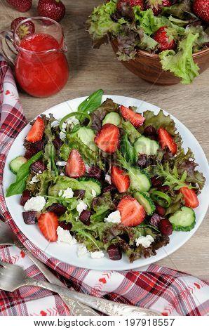Salad of vinaigrette with strawberries tender feta and strawberry sauce. Vertical shot.