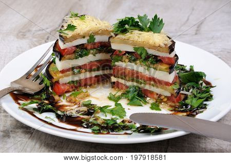 Appetizer from eggplant slices of mozzarella combined in a pile with tomatoes spilled with herbs seasoned Parmesan cheese. In section