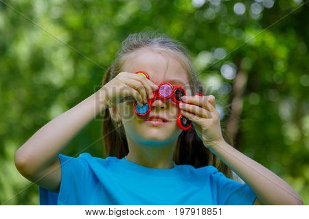 Little girl playing with fidget spinner. Child spinning spinner in park. Blurred background.