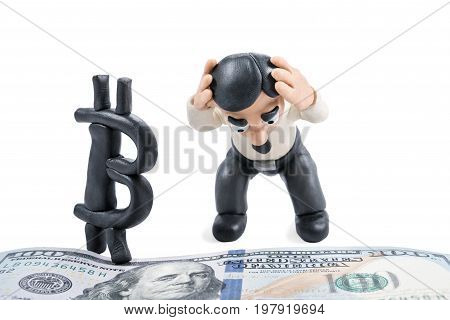 Plasticine businessman holds his head and is unhappy that bitcoin stepped on a hundred doller bill, isolated on a white background