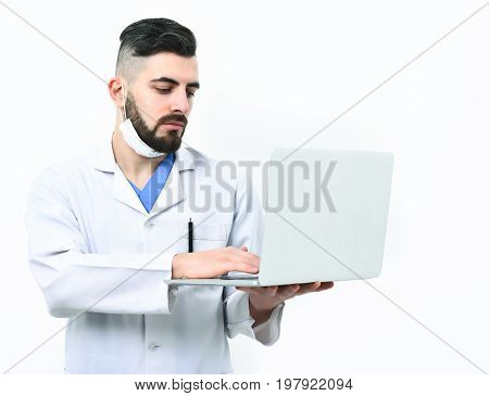 Doctor With Beard Uses White Laptop. Guy Wears Surgical Mask