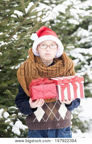 small boy or cute nerd kid in glasses hat sweater and fashionable knitted scarf holds red christmas or new year present boxes in winter outdoor at green fir tree with snow on natural background