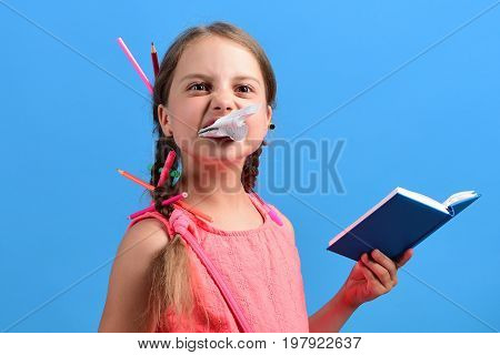 Girl Chews Piece Of Page From Blue Notebook