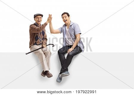 Senior and a young man high-fiving each other on a panel and looking at the camera isolated on white background