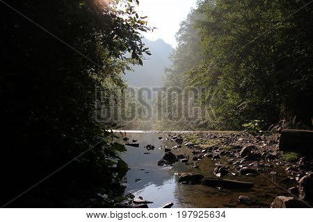Haze over mountain river early in the morning