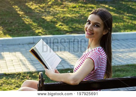 Smiling girl sitting on a wooden bench reading a book. Pretty young girl turns head backwards during reading a book in the park. Side view