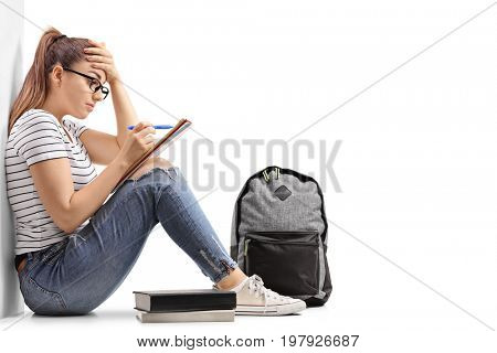 Teenage student having difficulty studying and leaning against a wall isolated on white background