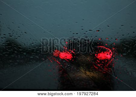 Car light seen through car window while driving during rain