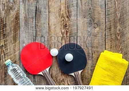 Sport background. Traning cocept. Ping pong racket, towel and water on wooden background top view.