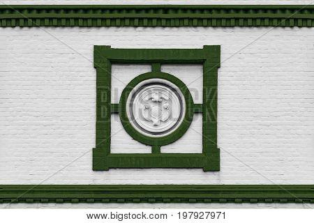 Stuck an einer weissen Hausfassade mit grünen Farbakzenten