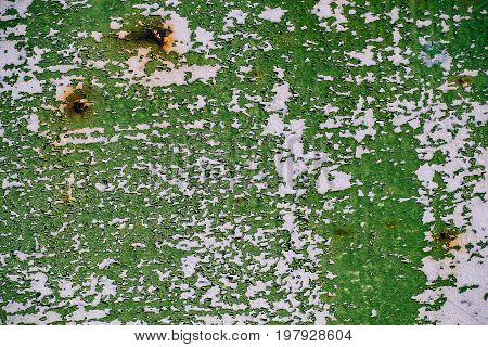 gray painted metal wall with cracked green paint rust stains sheet of rusty metal with cracked and flaky green paint metal background for design with copy space