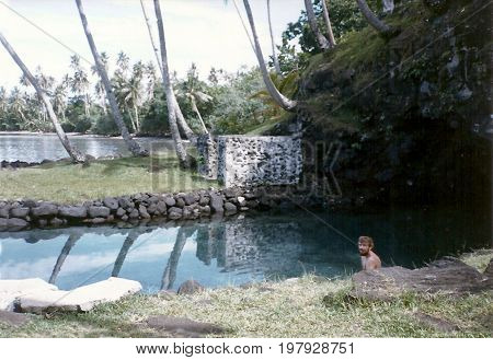 PIULA, UPOLU / SAMOA - CIRCA 1990: An American tourist sits in the Piula Cave Pool, also called the Fatumea Pool, a natural freshwater pool by the sea beneath the historic Methodist Chapel at Piula