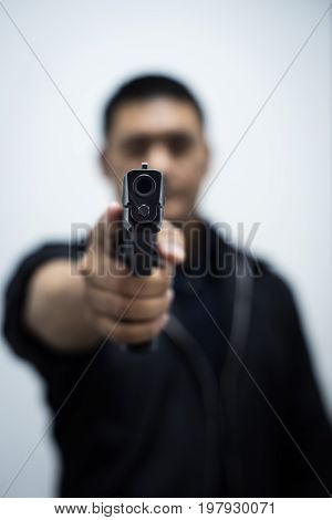 Man pointing gun at the target with one Hand on white background ,selective focus on front gun.