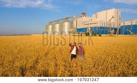 Aerial photo of two farmers standing in a wheat field and looking far discussing harvest and businness. Two men agronomists with grain elevator terminal on background.