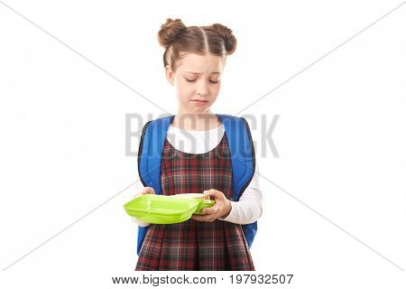 Portrait of cute girl in school uniform standing with lunchbox against white background