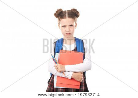 Portrait of displeased girl in school uniform with backpack holding textbooks and pencils against white background