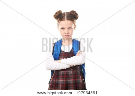 Portrait of cute girl in school uniform with backpack standing with displeased face against white background