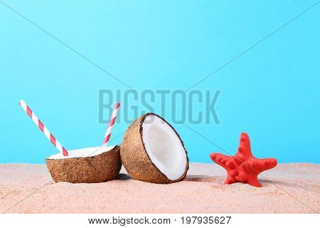 Half of coconut with starfish on beach sand