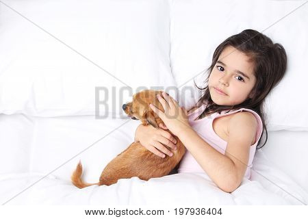 Beautiful little girl with dog sleeping in white bed