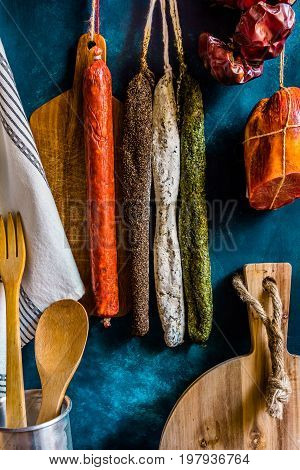 Assortment of traditional Spanish charcuterie meat sausages kitchen utensils towel wood cutting board rustic interior