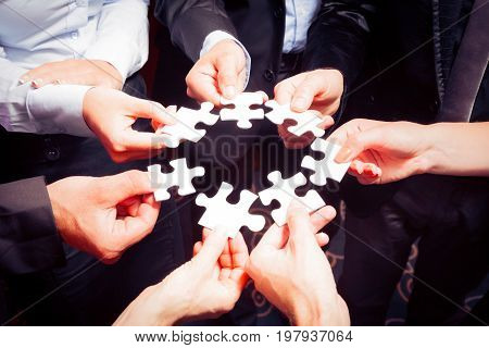 business team with jigsaw puzzle pieces: everyone is contributing their part to the big solution.