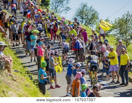 Col du Grand ColombierFrance - July 17 2016: Group of cyclists including Thomas De Gendt in Polka Dot Jersey riding on the road to Col du Grand Colombier in Jura Mountains during the stage 15 of Tour de France 2016.