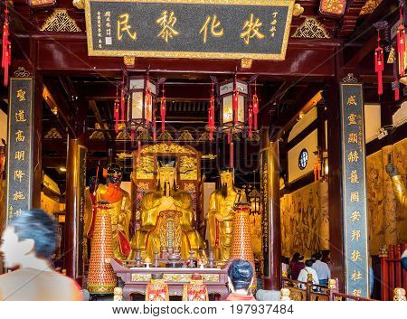 Shanghai, China - Nov 6, 2016: Inside the 600-year-old Old City God Temple. Statues of Taoist Deities are derived from famous ancient generals and judges. Hall is bustling with visitors. Low-light image.