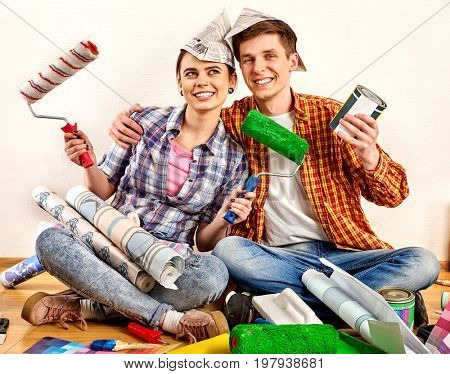 Repair family by happy couple building home. Quarrel family because of renovation in new apartment. Mad woman and man in newspaper cap renovation apartment. Happy newlyweds in a new house.