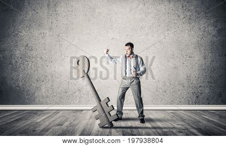 Determined businessman in concrete interior breaking with fist stone key figure
