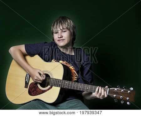 A teenage boy playing a guitar while seated