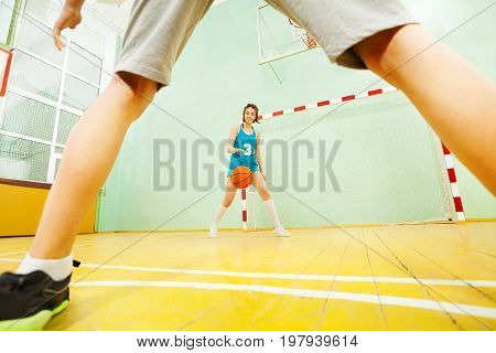 Portrait of teenage Asian girl dribbling basketball during the indoors match
