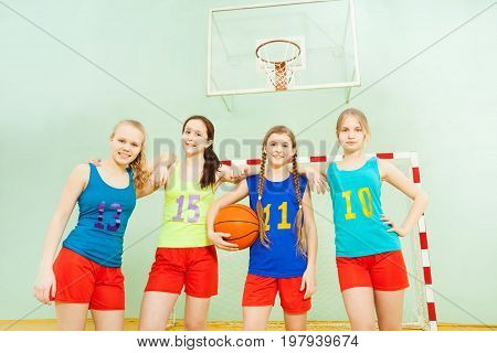 Female basketball players, beautiful teenage girls in uniform, standing together with ball in gymnasium
