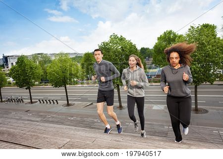 Group of three young athletes running upstairs on city stairs during outdoors cardio sport workout