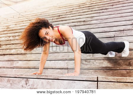 African sportswoman doing push-ups, exercising outdoors on city stairs, looking at camera