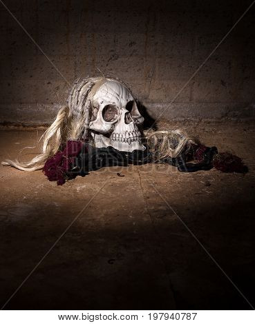 Scary human skull on a dirty stone floor and creepy background