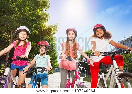 Portrait of happy bike riders, three preteen girls and a boy, standing together in line at summer park