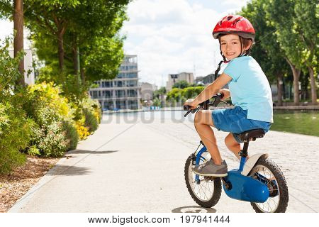Back view portrait of five years old boy in safety helmet cycling at city park in summer