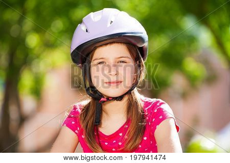 Close-up portrait of beautiful preteen girl in safety helmet looking at camera