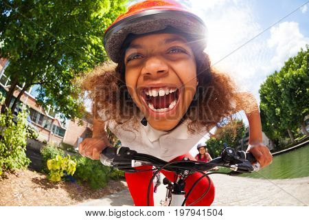 Close-up portrait of smiling African girl in safety helmet riding her bicycle at sunny day in full speed