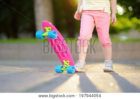 Closeup of skateboarder legs. Kid riding skateboard outdoor. Child practicing outside.