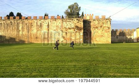 Chidren playing in Pisa Italy on the grass