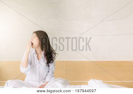 Asian woman yawing after wake up in the morning in bed with sunlight