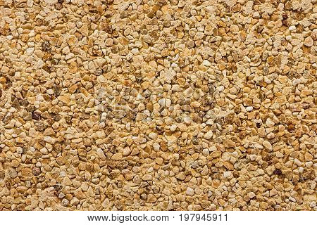 Wall texture uneven grainy background colorful pebbles drake stones brown beige yellow grungy texture pattern