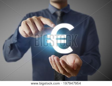 Businessman with euro currency symbol coming from hand on blue digital light background, financial concept
