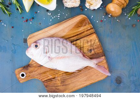 fresh sea fish preparation - pink dorada fish bream on cutting board with oil and spices