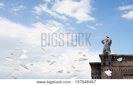 Frustrated businessman sitting on roof and closing ears with hands
