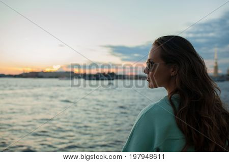 Young And Beautiful Girl Sitting On The Embankment Of The River. She Looks At The Sunset And Ships P