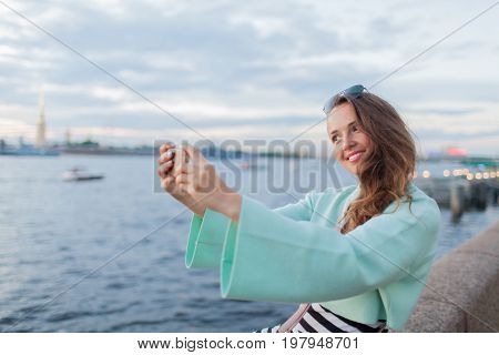 Young And Beautiful Girl Sitting On The Embankment Of The River. She Looks At The Sunset And Taking