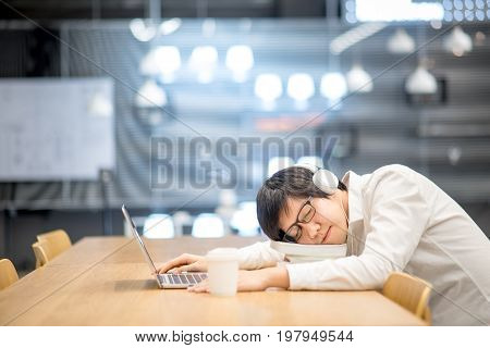 Young Asian man university student take a nap on book stack during doing homework in library college lifestyle concepts