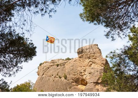 Spanish Flag (estelada) On The Mountain In The Forest. Against The Background Of The Blue Sky, Catal
